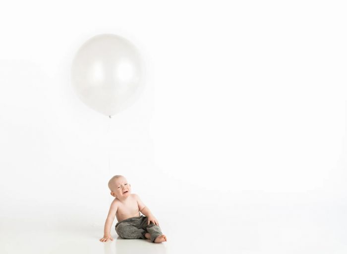 A baby boy crying under a white balloon