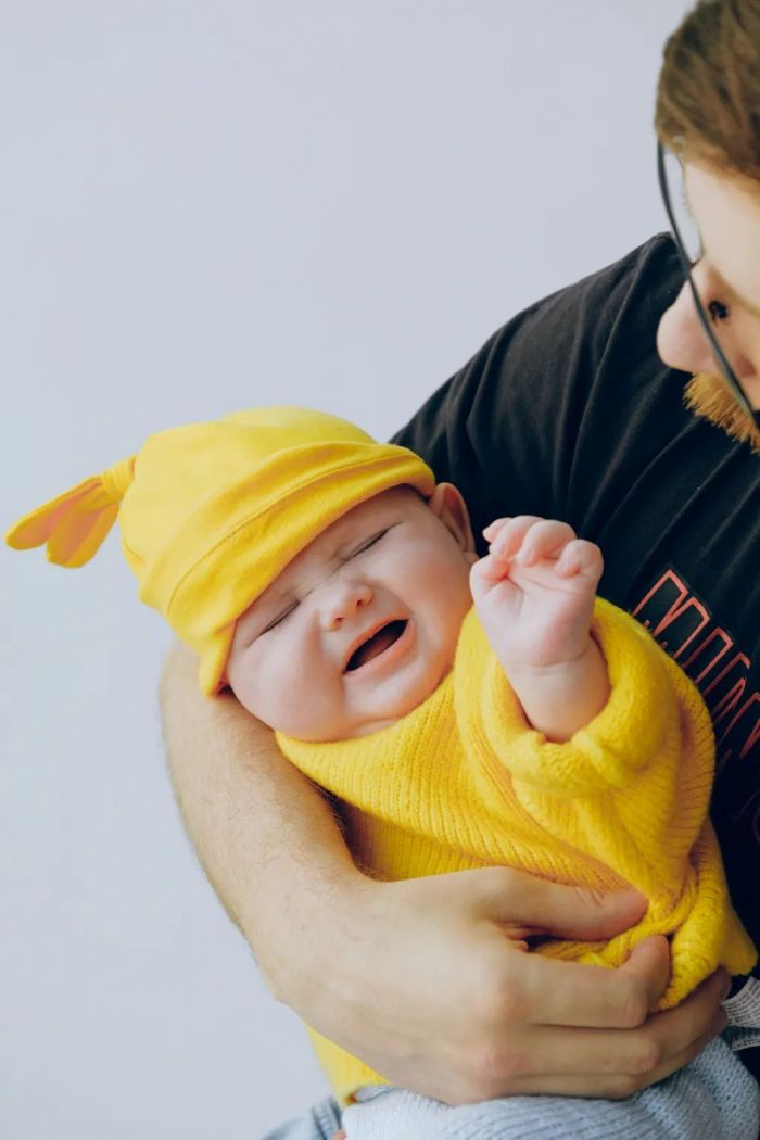 A crying baby in a yellow outfit