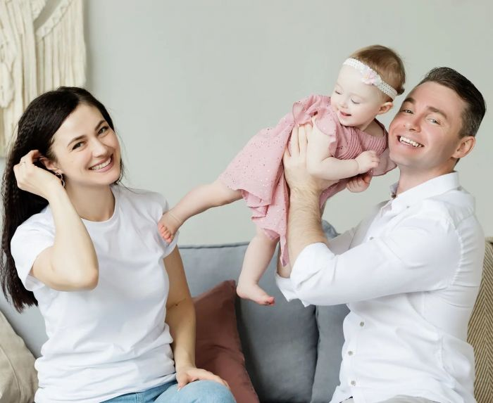 A family posing together in white on the sofa