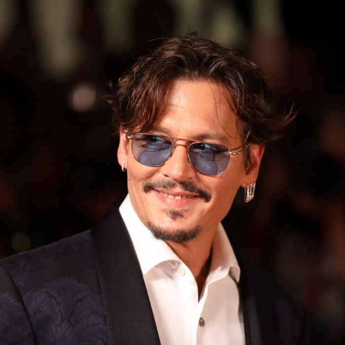 Actor Johnny Depp wearing blue sunglasses with a smile