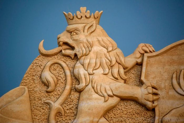 A sand sculpture of a lion eating fire