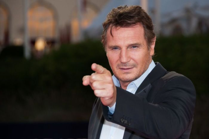 Actor Liam Neeson wearing a suit and pointing his finger