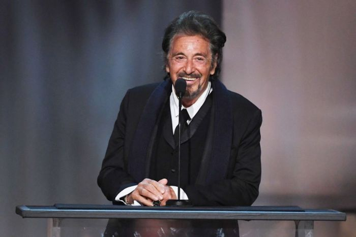Al Pacino in a suit speaking in a microphone on stage