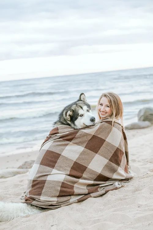 A dog and his owner cuddled up at the beach