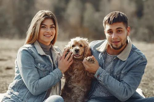 A couple wearing denim posing with their adorable dog