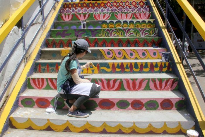 A colorful staircase in India with a girl sitting on it