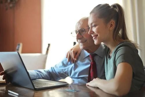 A young woman sitting by a laptop with an elderly man