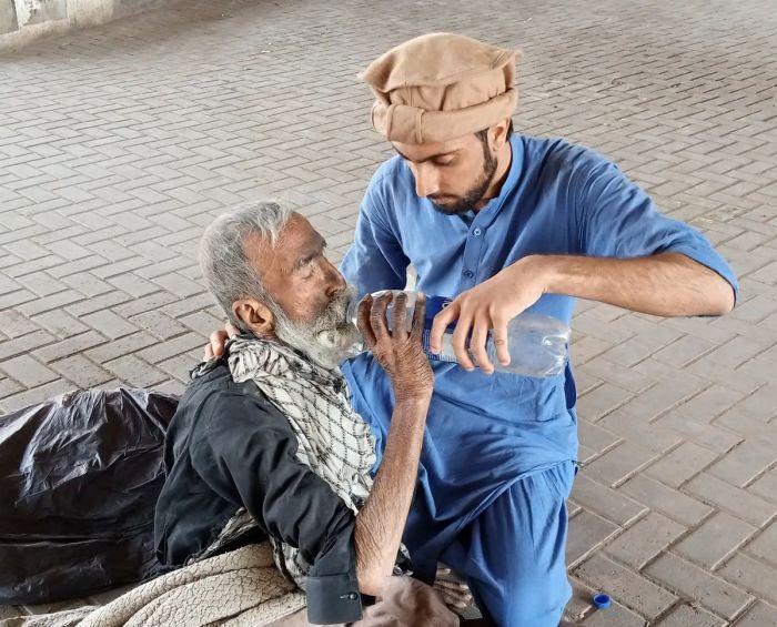 A man wearing blue giving a homeless man water