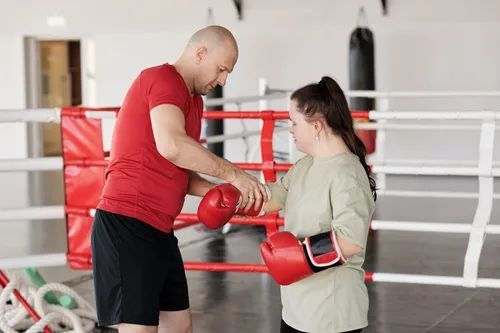 A girl learning to box from a male teacher