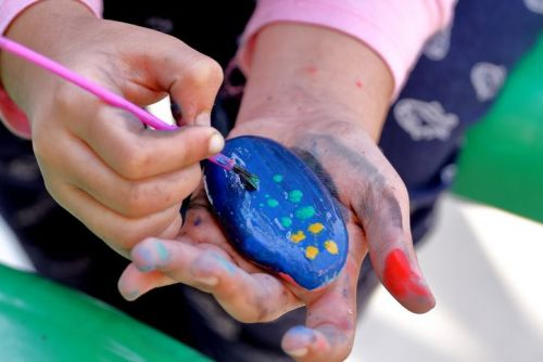 child painting a rock