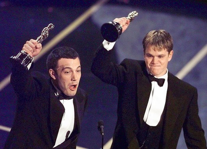 Matt Damon and Ben Affleck holding up their oscars together