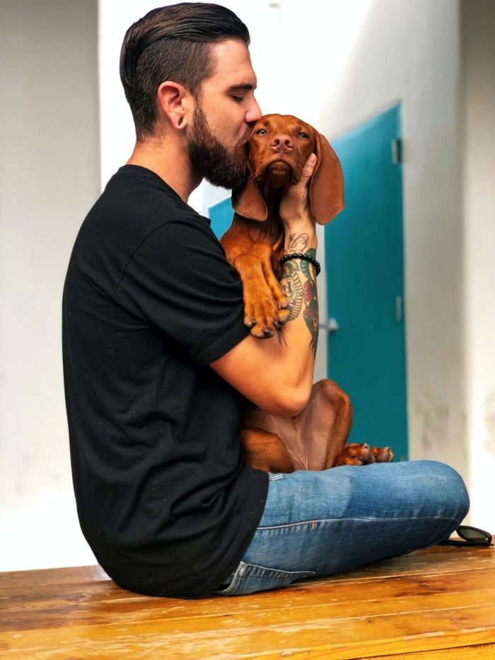 A hipster man kissing his adorable dog