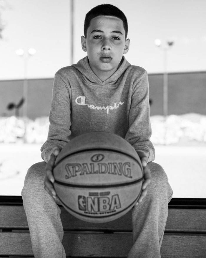 A boy pictured in black and white holding a basketball