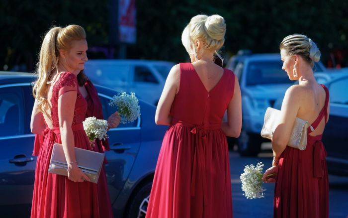 Three blonde woman dressed in red standing in a parking lot