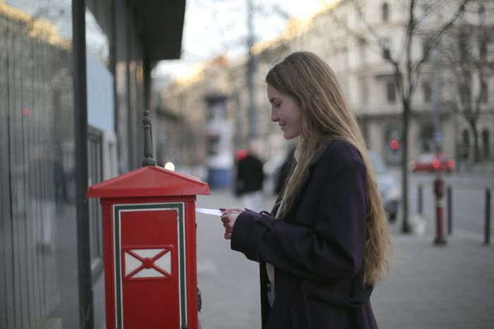 A girl putting a letter in a mailbox