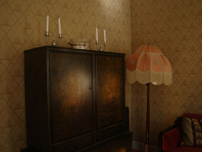 A wooden cabinet in an old room with a pink lamp