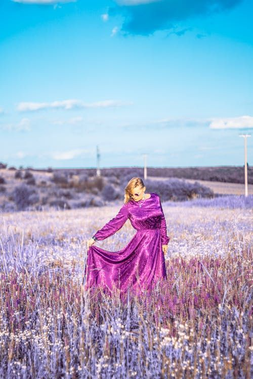 A woman in the fields wearing a long purple dress