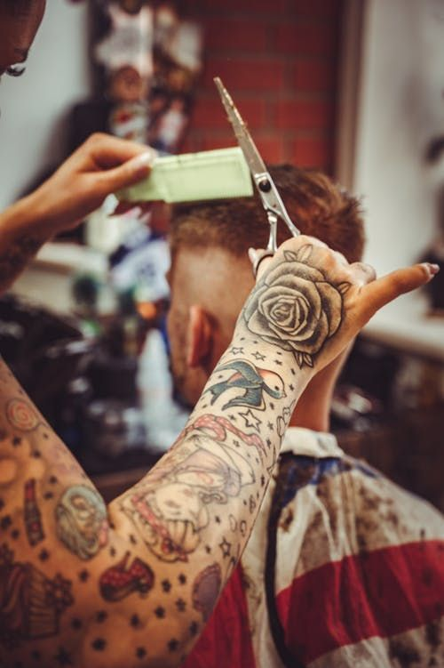 A person with tattooed arms giving a man a haircut