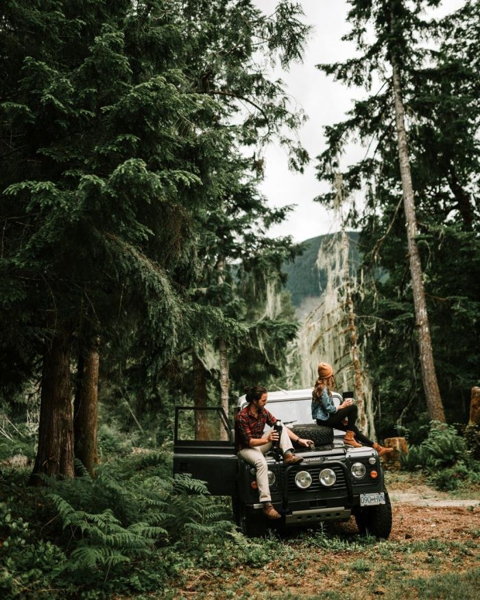 A couple sitting on a jeep in the woods