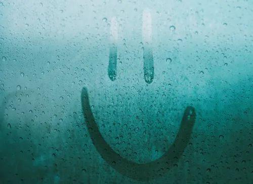 A happy face drawn onto a rainy window