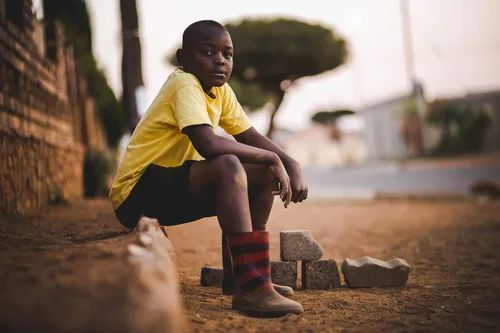 An African boy sitting on a ledge