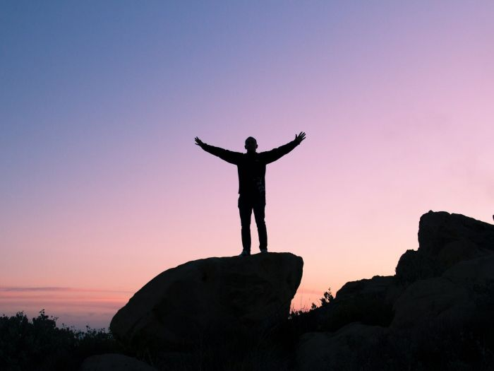 A silhouette of a man standing on a rock at sunset