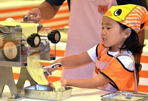 little girl making noodles