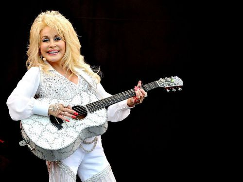 Dolly Parton wearing white and playing the guitar at Glastonbury Festival