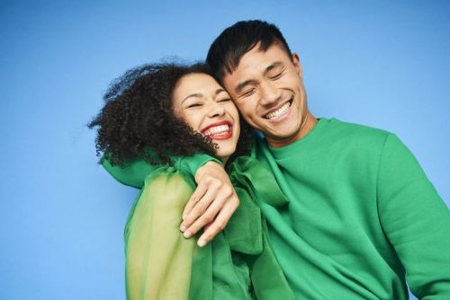 Man and woman wearing green clothes hugging in front of blue background