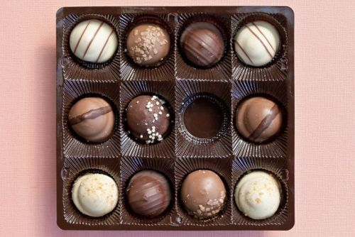 Overhead view of chocolates in a box, with one missing.