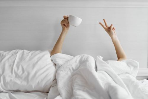 Woman under the bed covers making a peace sign with one hand and holding a tea mug with the other