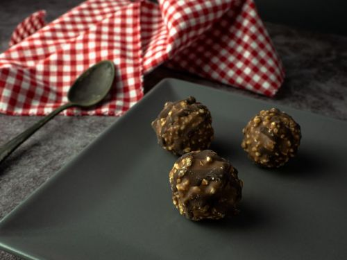 Homemade chocolate crunchy chocolates with hazelnut pieces and nuts in a gray square plate on a dark background with a rustic napkin of red and white squares and an old alpaca spoon
