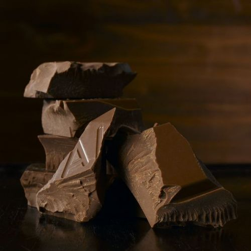 Pieces of chocolate on brown wood table