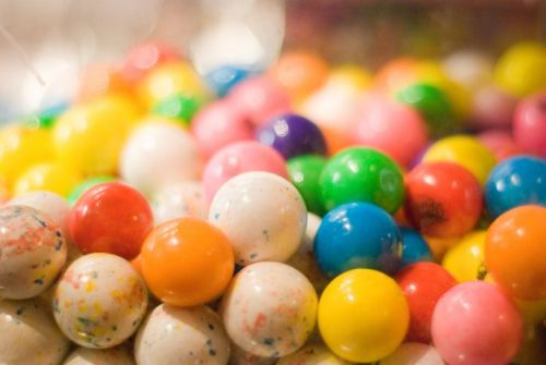 Colorful candy gumballs in a vending machine.