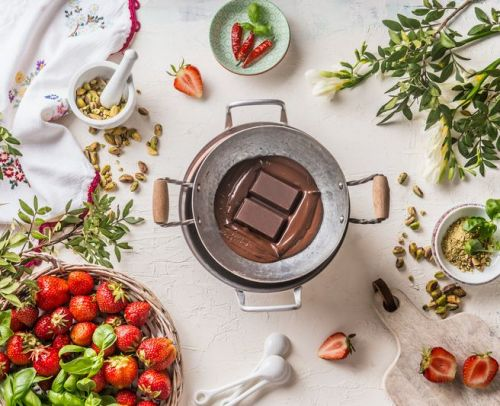 Pot with melted chocolate on white kitchen table with strawberries
