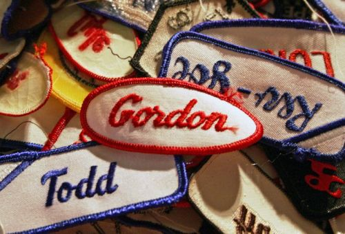 A pile of embroidered service industry uniform name tags; the names of Gordon and Todd are visible