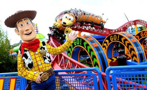 """Sheriff Woody poses in front of the """"Slinky Dog Dash"""" ride at Disney World"""