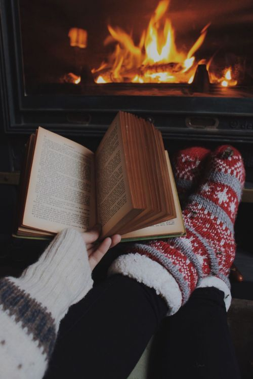 Woman reading book in front of a fireplace