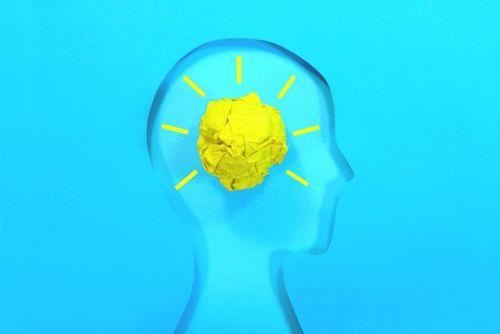 Yellow crumpled paper ball light glowing inside a paper human head