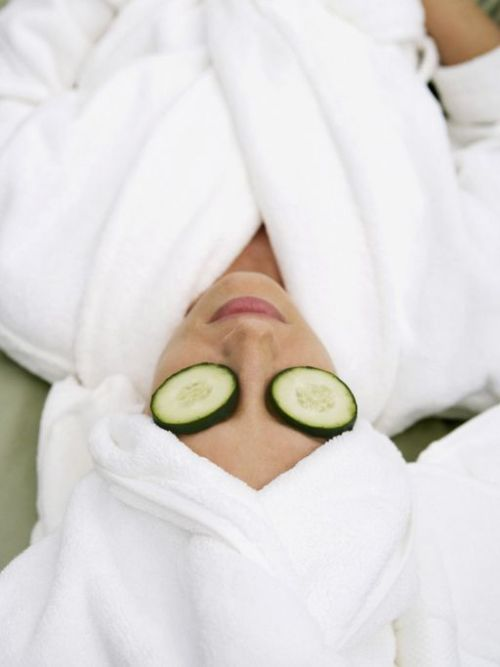 Woman wearing bathrobe with slices of cucumbers on eyes