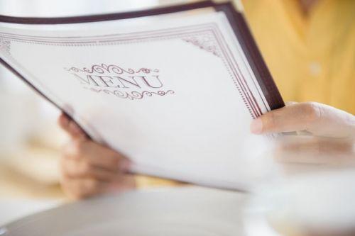Person holding up restaurant menu
