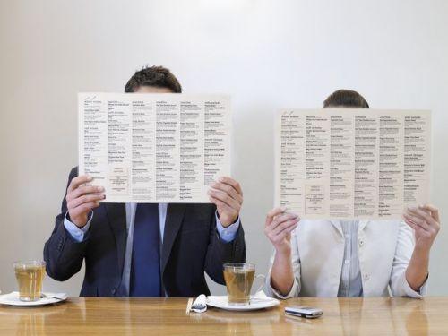 Two people hiding their faces behind restaurant menus